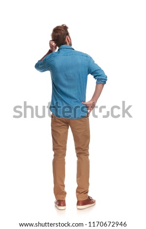 back view of a young casual man scratching his head on white background