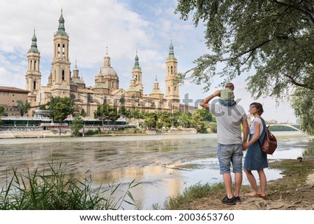 Back view of a young family, parents and baby, doing sightseeing in Zaragoza. They are standing at Ebro river bank and enjoying Basilica del Pilar view. Family holidays. Foto stock ©