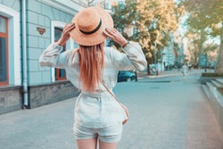Back view of a young female wanderer out sightseeing in a foreign city during weekend overseas, trendy woman traveler with a rucksack on her back walking on unfamiliar street during summer adventure