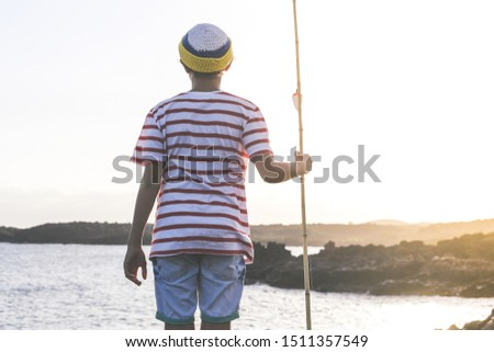 Back view of a young fisherman with with fishing pole in hand looking the sea. Sailor boy with wool cap and a striped t-shirt enjoying a summer evening. Lifestyle, outdoors, fun and carefree concept