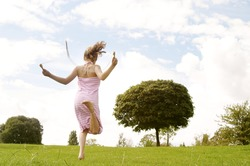 Back view of a young girl skipping in the park with a rope.