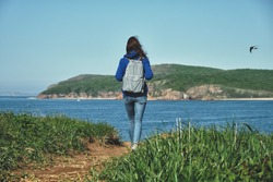 back view of a young girl with long hair and backpack walks alone along a path goes along a hill above the sea with a view of the island overgrown with grass. Social distancing and travel concept
