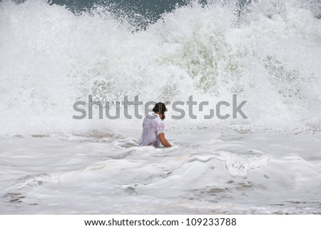 Back view of a young man in the sea facing a large wave on a windy day on holiday.