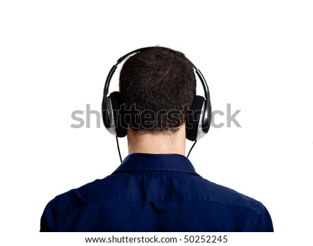 Back view of a young man listening music with headphones, isolated on white