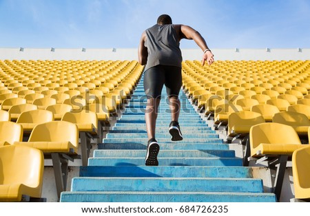 Back view of a young man running upstairs at a stadium ストックフォト ©