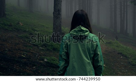 Back view of a young woman hiking in forest. Hiking woman walking in gloomy mystical forest - thriller scene. Wide-angle lens. Close-up