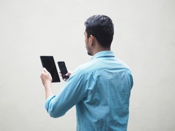 Back view of Adult Asian man wearing blue shirt holding and looking to mobile phone and tablet. Isolated on white