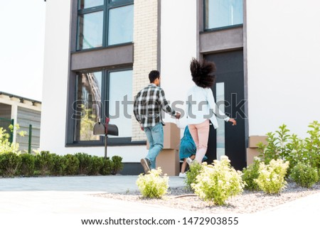 back view of african american family running to new house  #1472903855