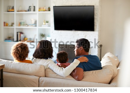 Back view of African American young family sitting on the sofa and watching TV together in their living room, close up