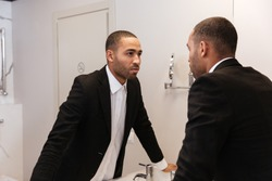 Back view of African man in suit looking at mirror in bathroom in hotel room