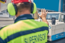 Back view of an airport worker in headphones directing a pushback driver at the airdrome