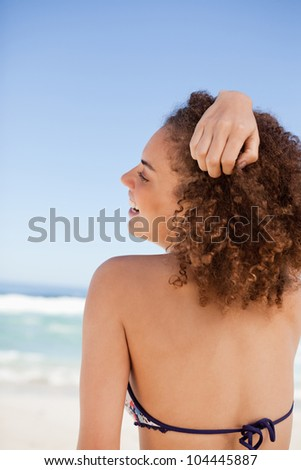 Back view of an attractive woman placing her hand on her hair in front of the sea