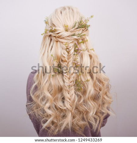 Back view of an elegant trendy hairstyle, interlacing curls and decorating with flower petals. Beautiful and well-groomed blonde hair #1249433269