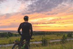 Back view of anonymous man in helmet admiring cloudy sundown sky during bicycle ride in summer evening in nature