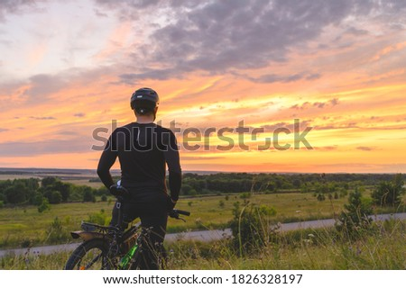 Back view of anonymous man in helmet admiring cloudy sundown sky during bicycle ride in summer evening in nature Foto stock ©