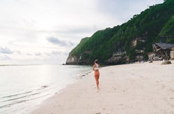 Back view of anonymous pensive female standing alone on sandy shore near calm water of sea against rocky hill covered with green plants in tropical country