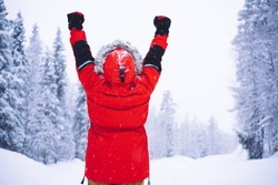 Back view of anonymous person in red outerwear raising clenched fists and celebrating victory on cold winter day near forest in Norway