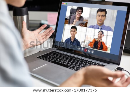 Back view of Asian business man or creative using laptop video conference talking with corporate team, meeting online, work from home and working remotely, group of people discuss about project report