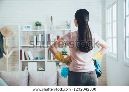 back view of asian housekeeper looking at the clean living room after she tidied up. young wife finished house chores putting hands in waist watching the bookshelf beside the sunlight window. Foto d'archivio ©
