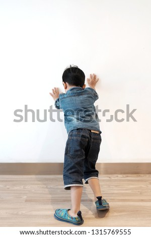 Back view of Asian kid 4 year old try to push the wall with two hands. schoolboy making great effort while setting against wall.  Concept never give up,