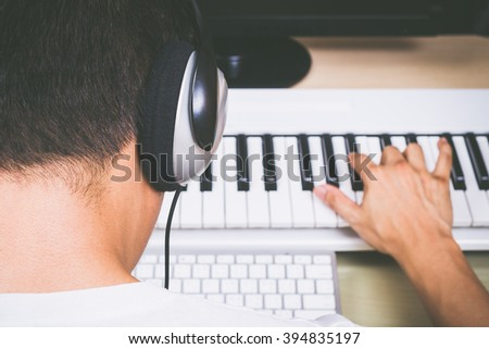 back view of asian male professional composer making songs with studio keyboard and computer. music production technology concept