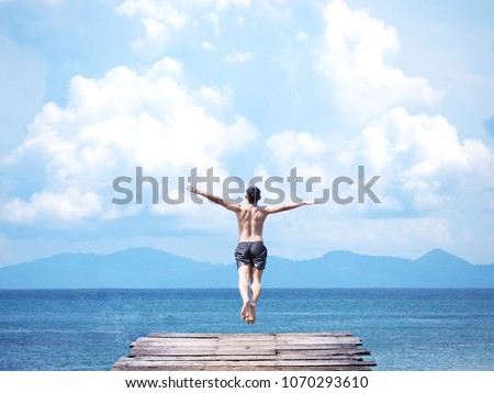 Back view of asian man jumping off wooden bridge into blue sea background. Flying freely to the sky. Summer vacation lifestyle. #1070293610
