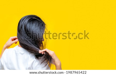 Back view of Asian woman holding damaged hair on yellow background. Hair loss and thin hair problem in woman. Dry and brittle black long hair need shampoo and conditioner for spa treatment.