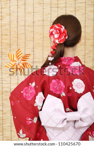 Back view of asian woman in clothes of kimono with toy pinwheel