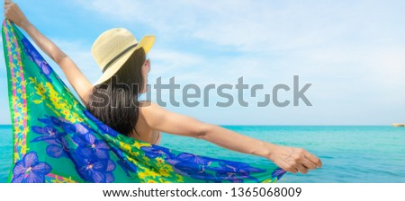 Back view of Asian woman wear swimsuit and opened arms at tropical beach on sunny day with beautiful blue sky and white clouds. Woman travel on summer vacation. Summer vibes. Happy girl.