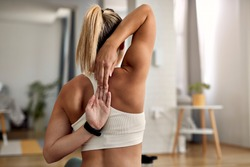 Back view of athlete stretching her arms and shoulders while exercising in the living room.