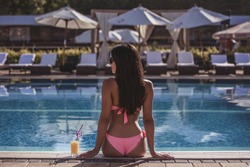 Back view of attractive woman in pink swimsuit resting near the pool