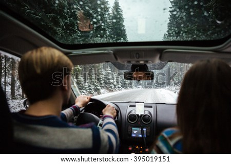 Back view of beautiful couple driving in car through winter forest
