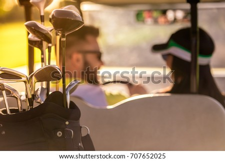 Back view of beautiful couple talking while driving a golf cart, golf clubs in focus