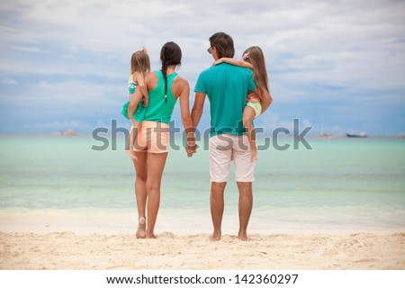 Back view of beautiful family with two daughters at exotic beach on sunny day