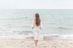 Back view of beautiful girl in a white linen dress walking by seaside