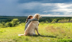 Back view of beautiful little girl hugging loyal dog in nature