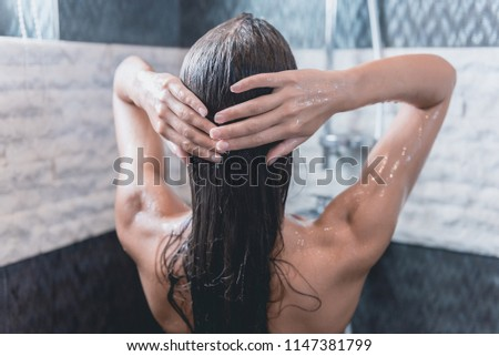 Back View of Beautiful Naked Young Woman Washing Hair while Taking Shower in Bathroom. Concept of Relaxation and Freedom at Home. Beauty at Morning Concept. Personal Hygiene at Morning.