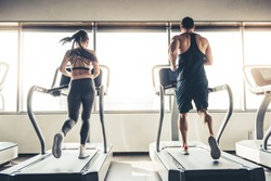 Back view of beautiful sports people running on a treadmill in gym