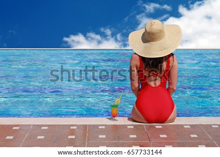 Back view of beautiful woman in bikini and large hat relaxing at pool with cocktails. Summer holidays, travel, vacation concept. Copy space. #657733144