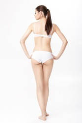 back view of beautiful young brunette woman with perfect sporty body in white lingerie on white background.