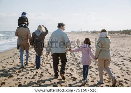 back view of big multigenerational family walking together on seashore