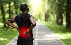 Back view of black sportsman touching sore zone on his back, having back pain during jogging by park, empty space