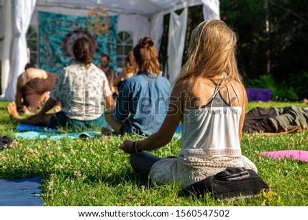back view of blonde girl with a diverse group of people enjoying outdoor meditation session during a woodland spiritual gathering