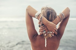 Back view of boho styled and tanned girl wearing ethnic indian silver jewelry looking at horizon on the beach in Bali