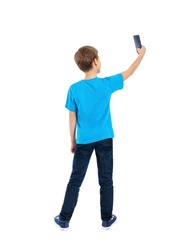 Back view of boy in t-shirt and jeans using a mobile phone isolated on white background