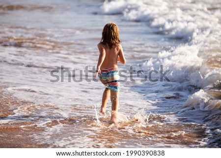 Back view of boy running beach near the seaside. Excited amazed kid having fun with running through water in ocean or sea. ストックフォト ©