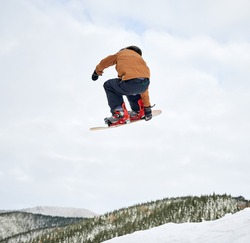 Back view of boy snowboarder in winter jacket and helmet jumping in the air. Adorable kid making jump with snowboard while sliding down snowy hill in winter mountains. Concept of extreme winter sport