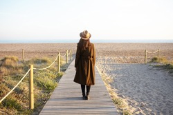 Back view of brunette girl in hat and coat standing on boardwalk by seaside, contemplating beautiful landscape in front of her. Unrecognizable young female in overclothes walking outdoors alone