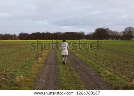 Back view of brunette woman in winter clothing walking along a dirt road between green fields or grassland, a kale field can be seen in the background, picture taken in Oldenburg, Lower Saxony Germany