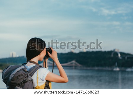 back view of brunette woman with backpack taking photo